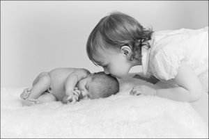 big sister kissing her newborn sister on the head