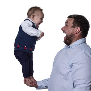 dad holding his young son in one hand - both are laughing