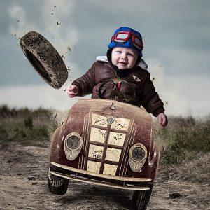 Family portrait - little boy in a dirty racing car