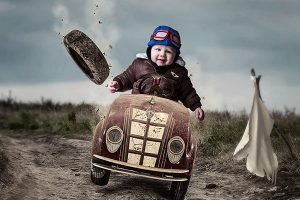 toddler in a car with the wheel flying off.